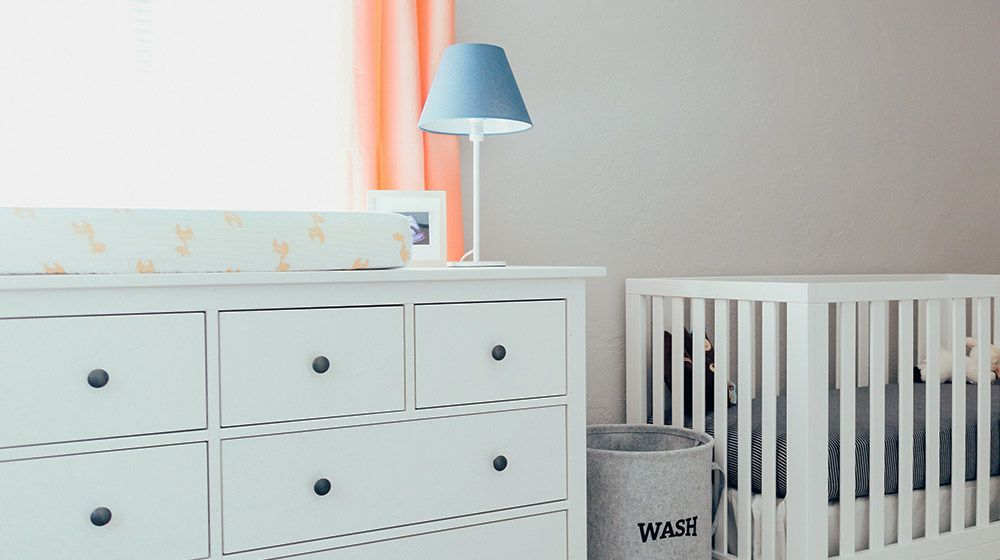 white dresser and crib in a simple nursery