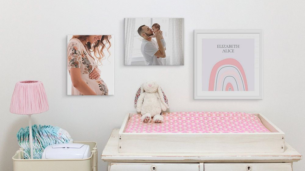 personalized photos and art on the wall above changing table in a nursery