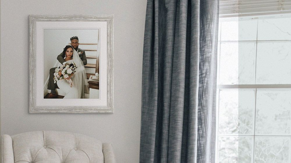 A framed print of a couple's wedding hanging on a wall in a living room