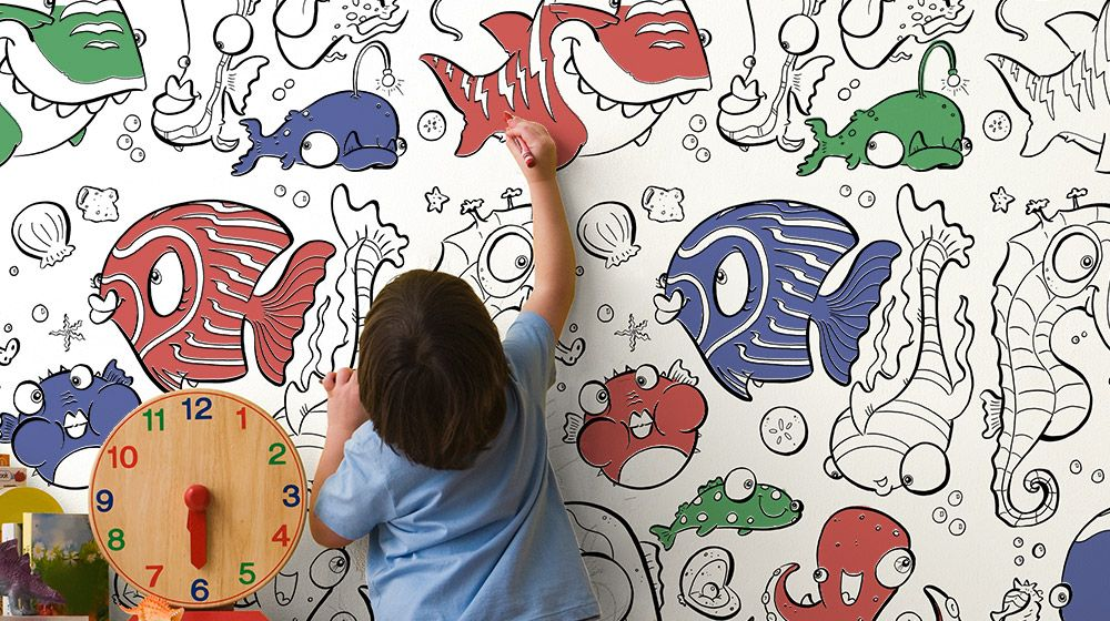 A child coloring a removable coloring wallpaper design