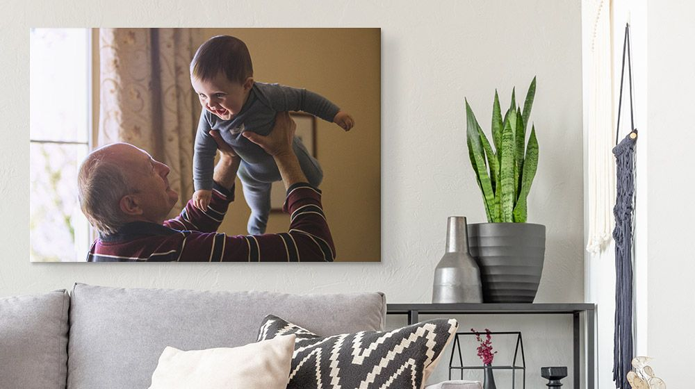 A canvas print of a grandfather holding up a child and hanging over a couch