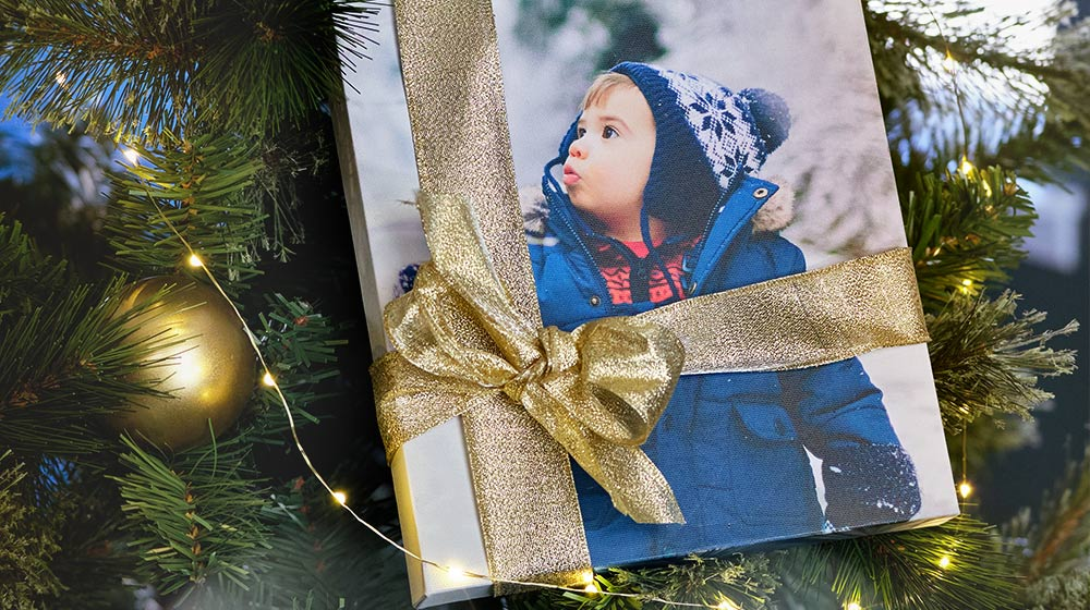 A gift-wrapped canvas print on a decorated Christmas tree