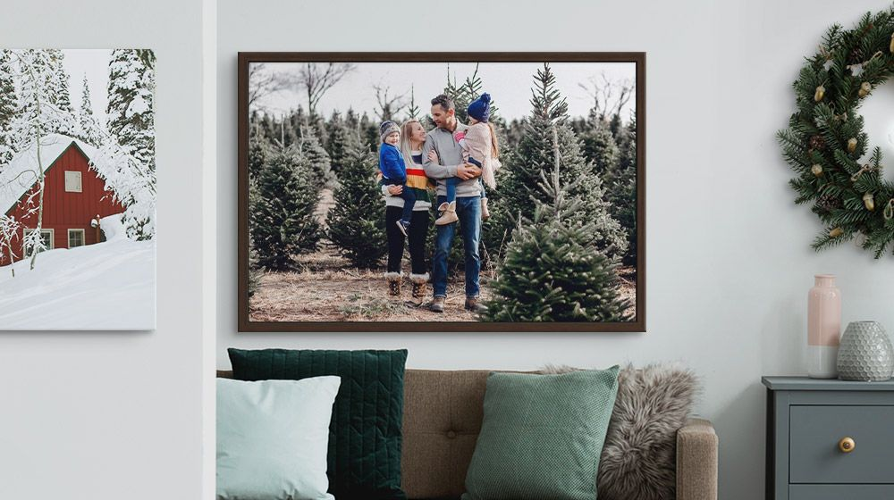 A framed canvas print of a family at a Christmas tree farm hanging over a sofa