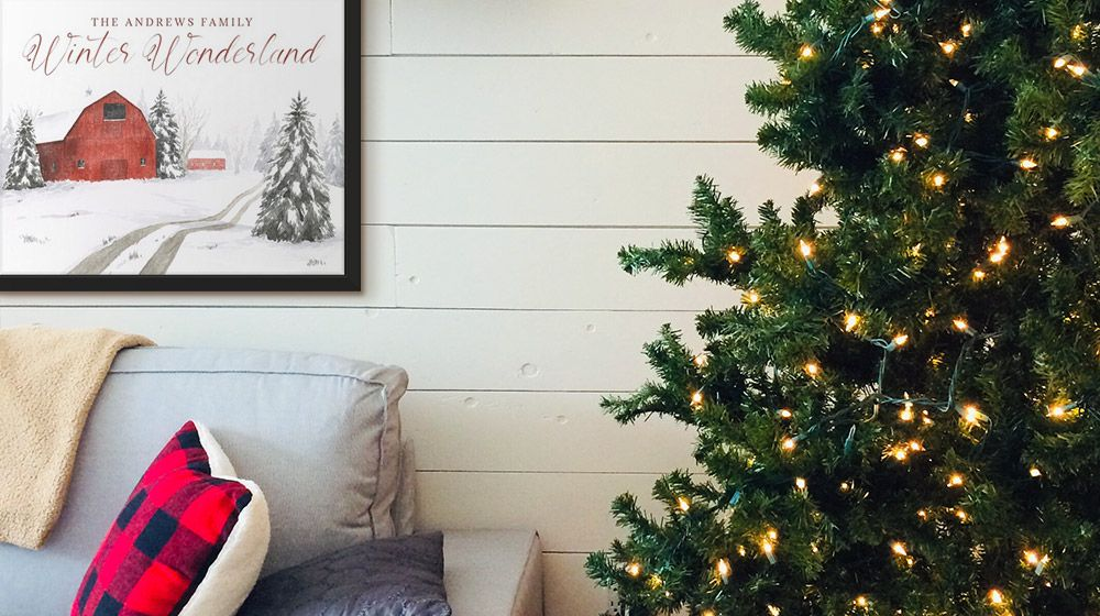 Holiday-themed, personalized word art hangs near a Christmas tree