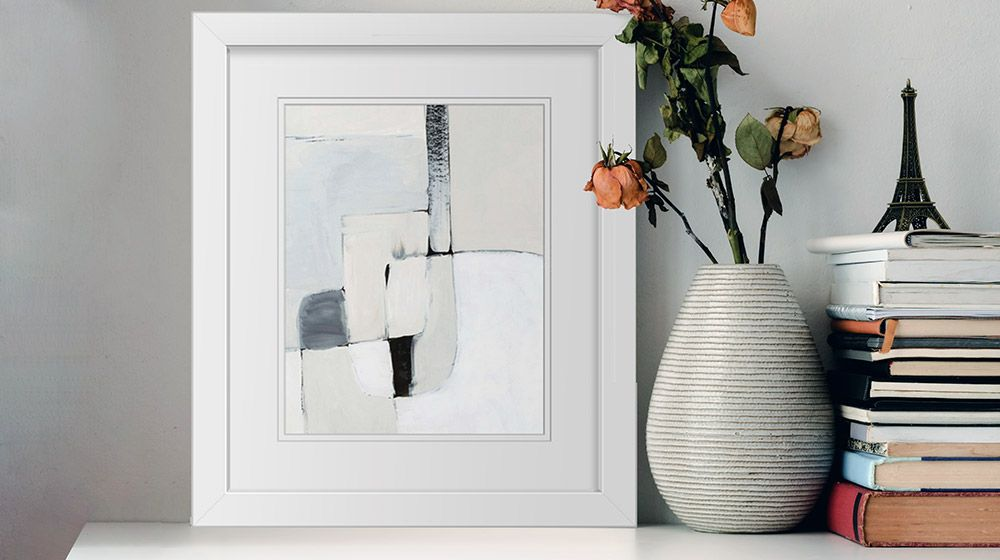 A framed print of a warm, minimalist abstract art piece sitting on a shelf next to some books