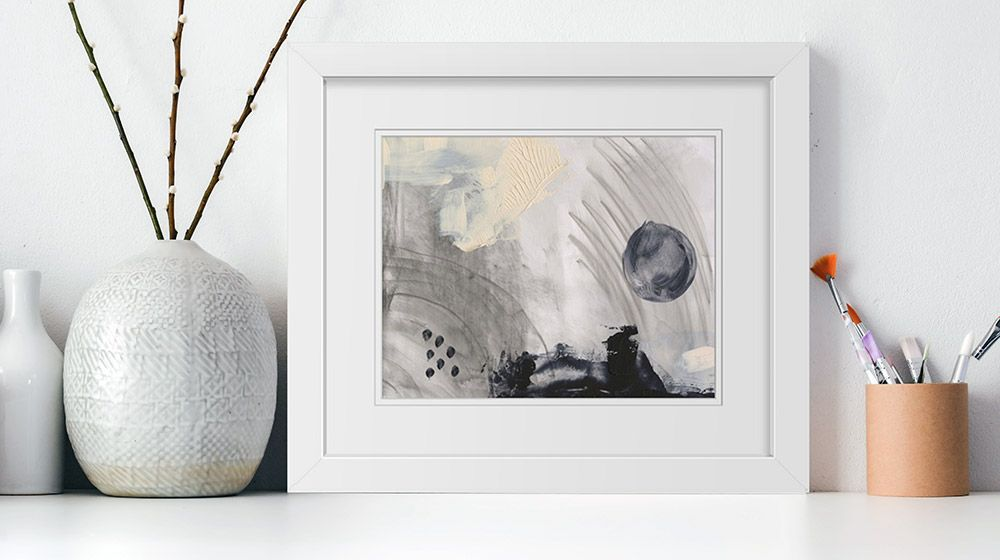 A framed print of a warm abstract painting sitting on a shelf