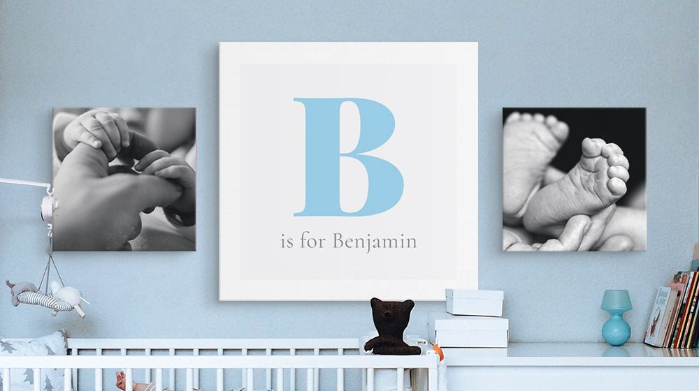 A monogram canvas print and two photo canvas prints hanging over a crib in a nursery