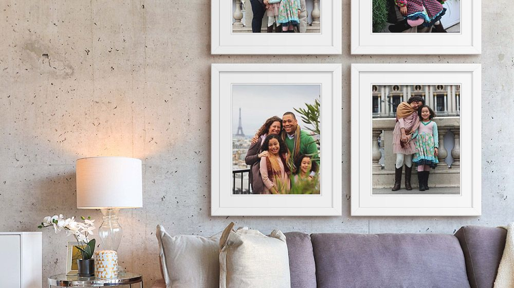 Family photos arranged in a square display above a velvet couch