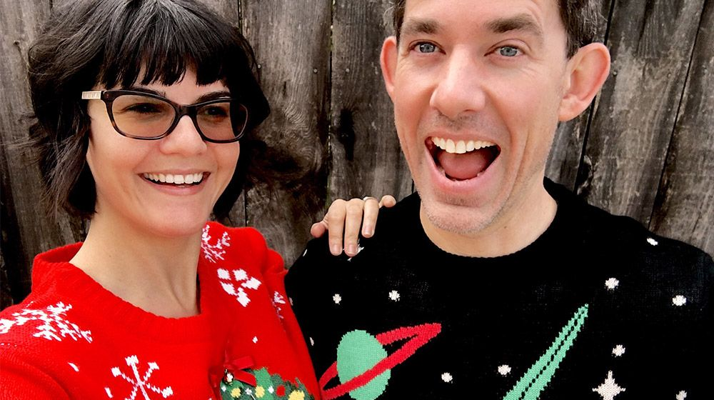 a couple wearing ugly holiday sweaters