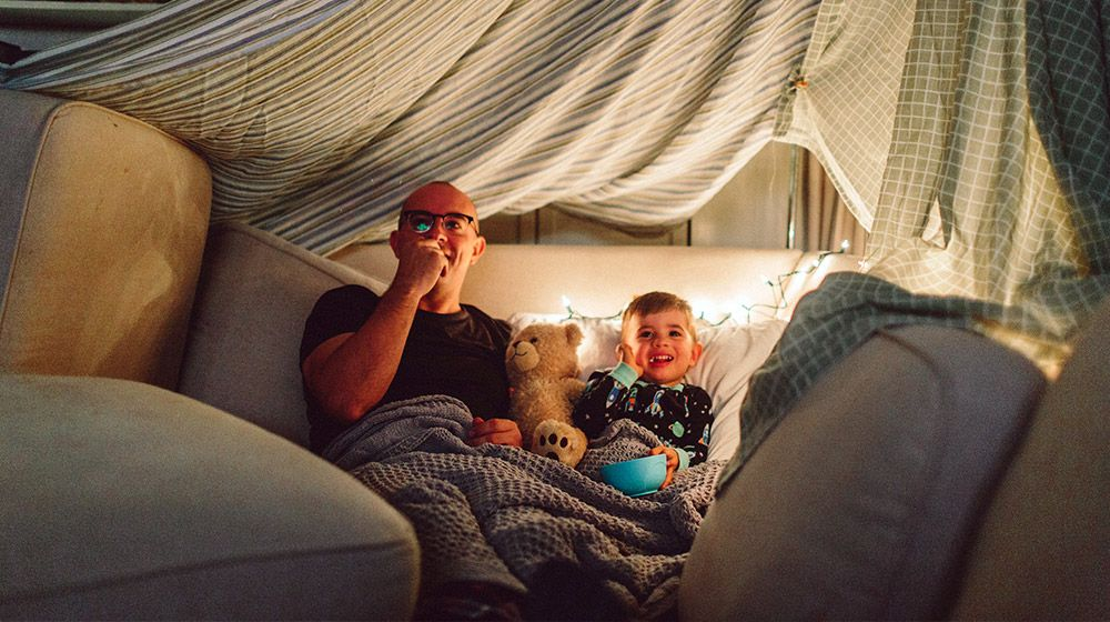 A father and son enjoy an indoor movie night