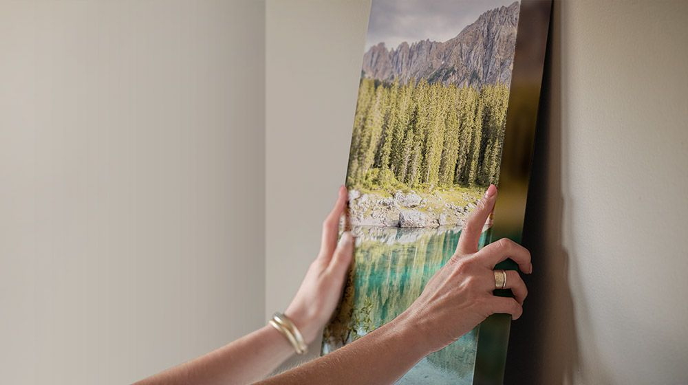 person easily hanging a canvas photo print on their wall of a forest and lake
