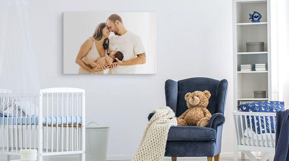 photo canvas print depicting parents with their newborn on a nursery wall