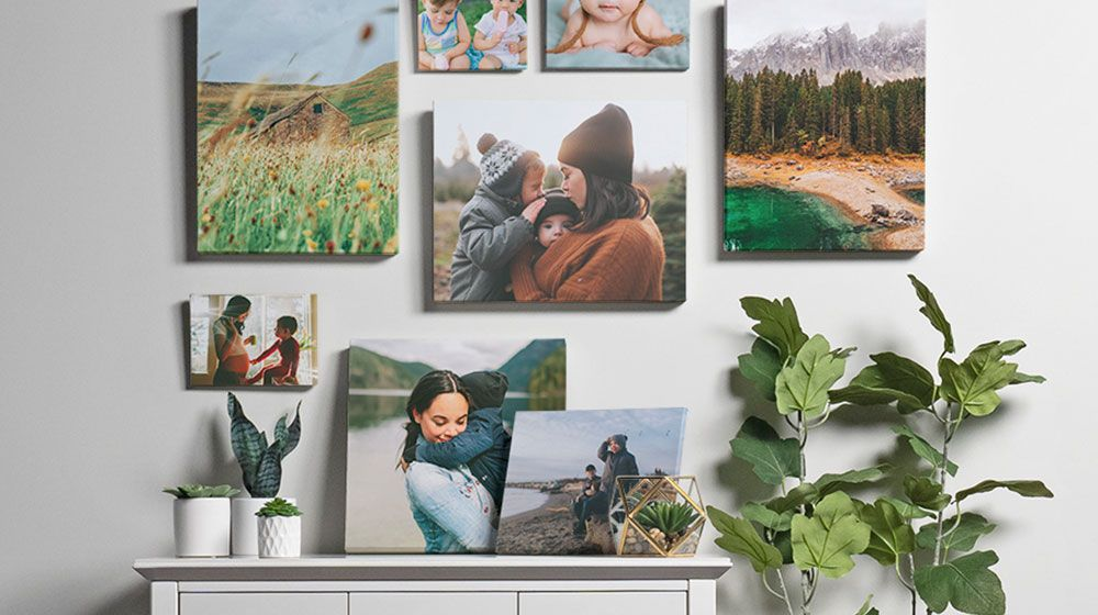 multiple canvas photo prints forming a gallery wall above a side table