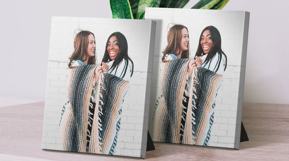 two tabletop canvases with picture of two best friends sitting on desk