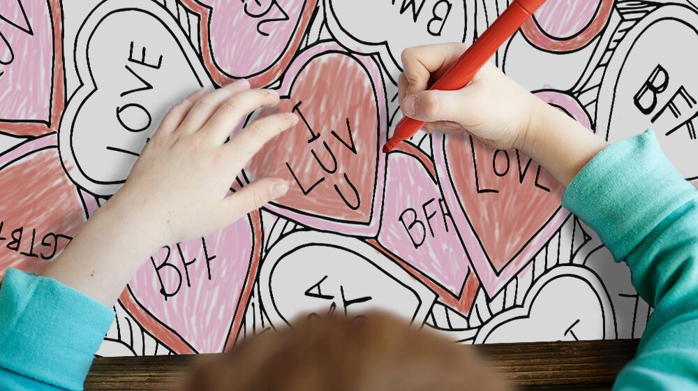 photo of boy coloring a valentine's day coloring canvas with red and pink markers