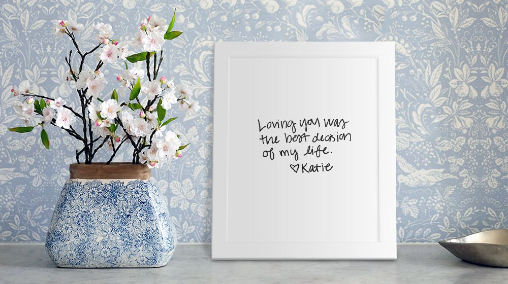 framed canvas of handwritten love letter, sitting on table next to vase of flowers