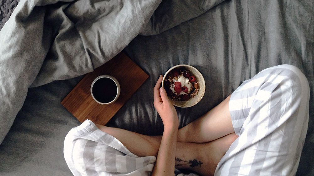 woman in striped pajamas on bed with breakfast bowl and coffee