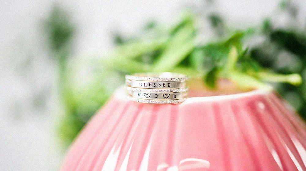 a pair of personalized diamond rings sitting on pink planter with green plant