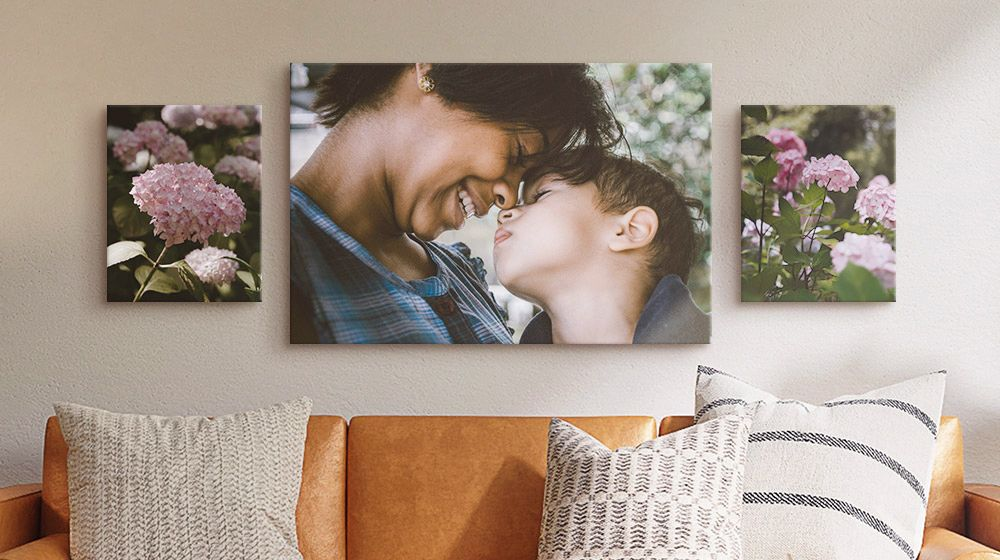 canvas of mother and son hanging above couch with two canvases of pink hydrangeas