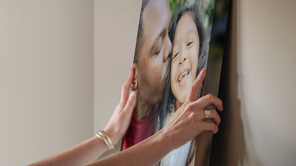 a woman hanging a canvas of a black dad and mixed daughter