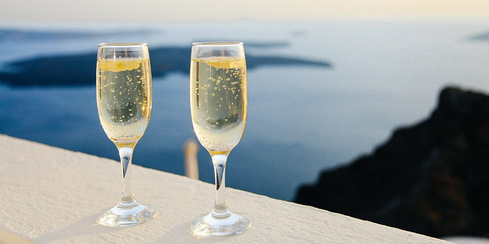a pair of champagne glasses sitting on ledge outside overlooking the ocean