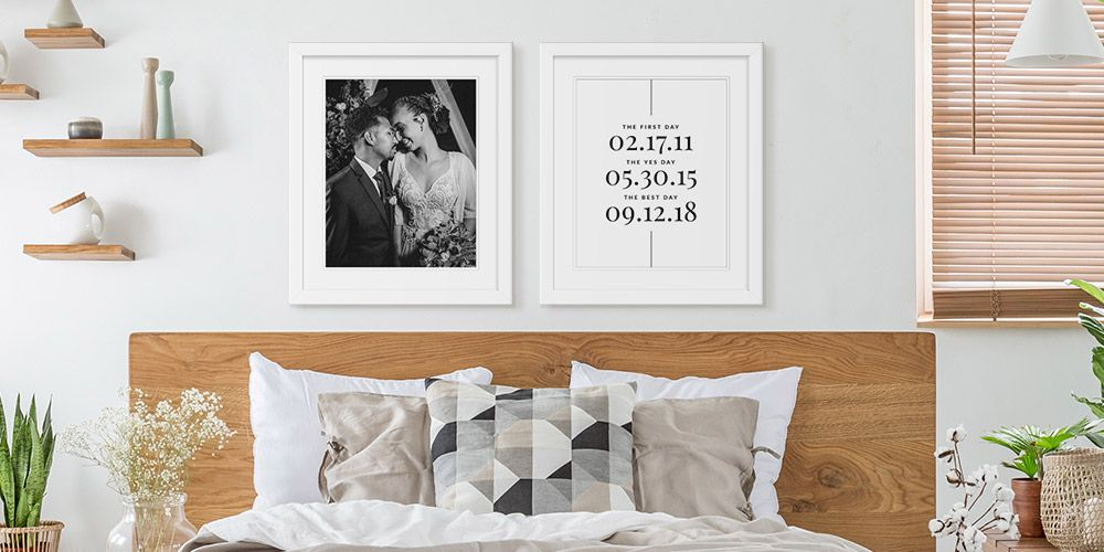 white framed wedding photo and personalized word art on wall above neutral themed bedroom
