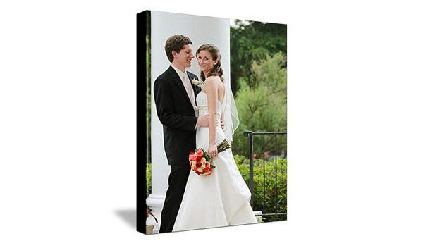 canvas of wedding couple standing next to pillar outside