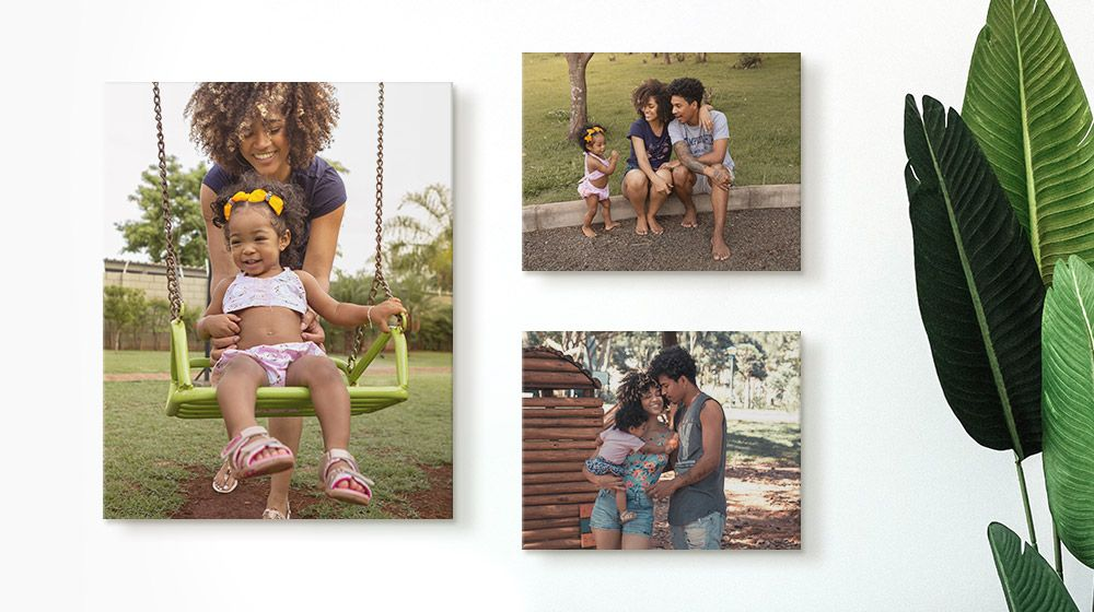 Three canvas prints of two parents and their child on a minimal white wall.