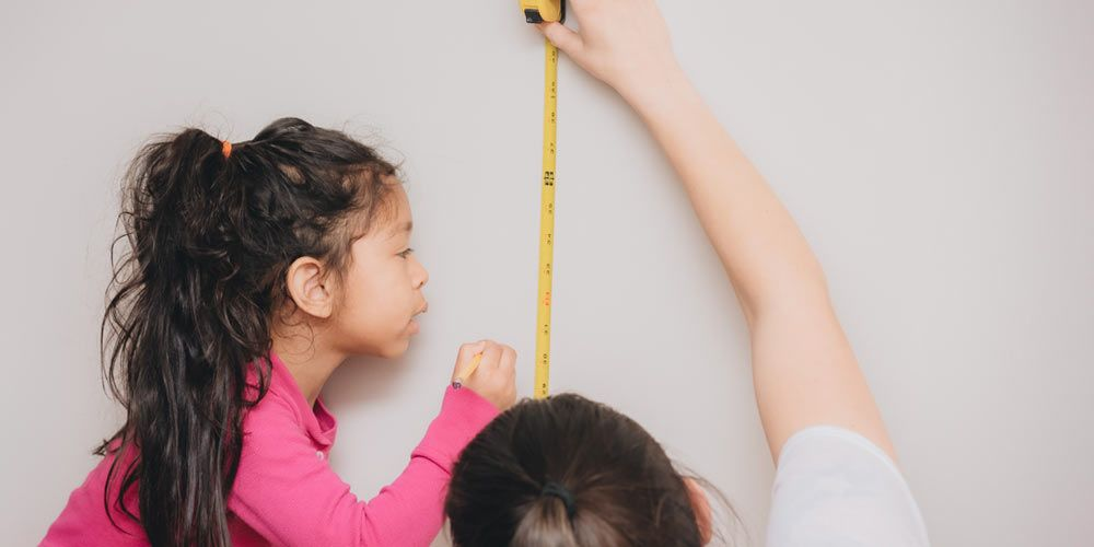 woman measuring empty wall space while young girl marks hanging spot with pencil