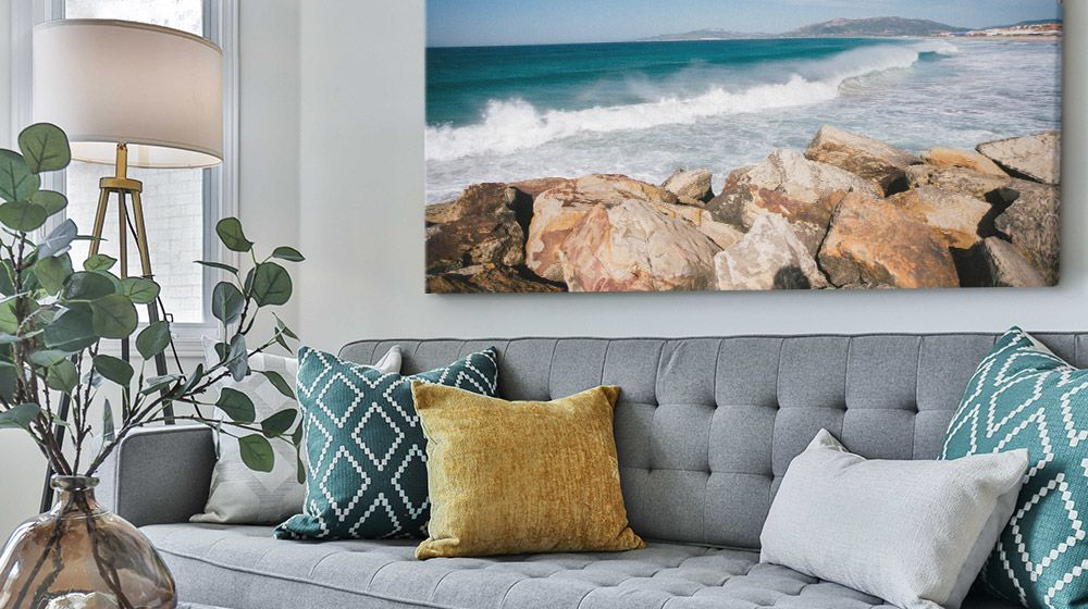 Large Canvas print of a beach over a gray couch in a contemporary living room.