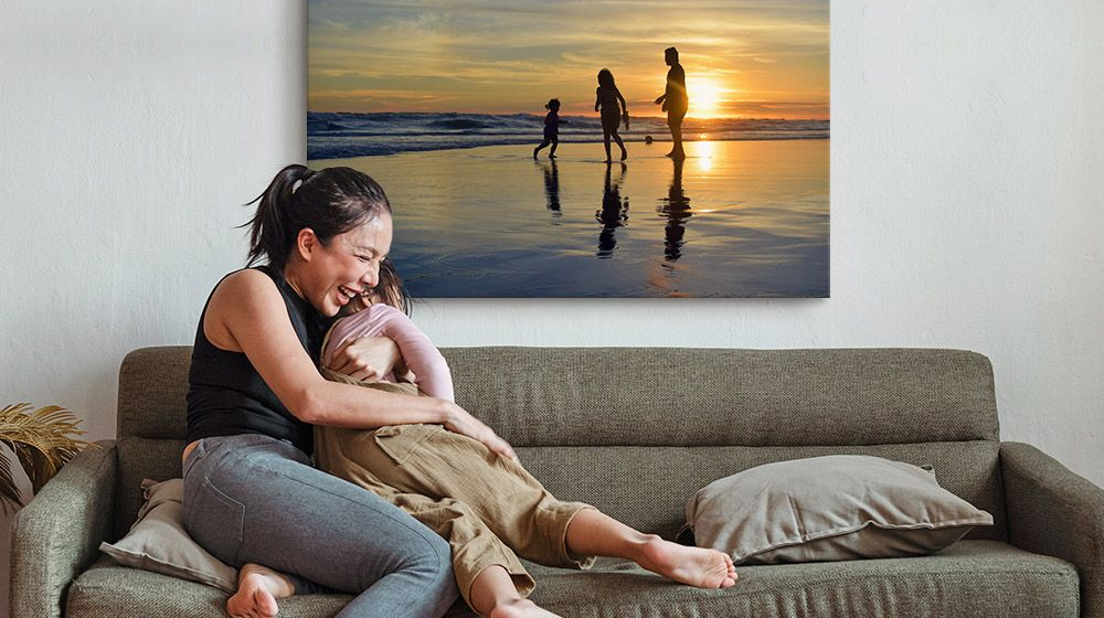 A mother and child embrace on a couch in front of a large canvas print of the beach.