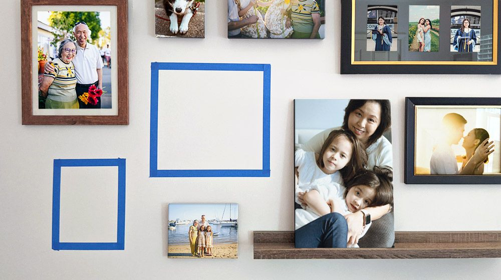 Photograph of a wall display featuring framed prints and canvases with two spots mocked up with painter's tape.