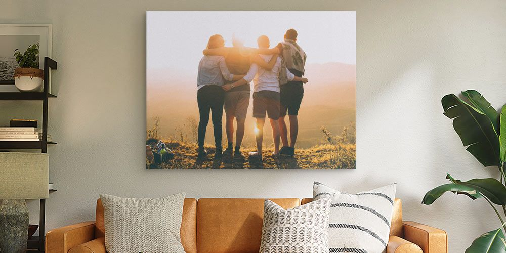 large canvas print depicting family photo at sunset over a leather couch