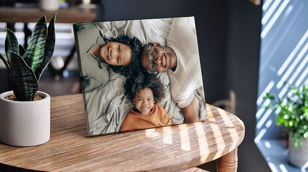 8x10 Tabletop Canvas of a dad and his two children leaning on a living room end table.
