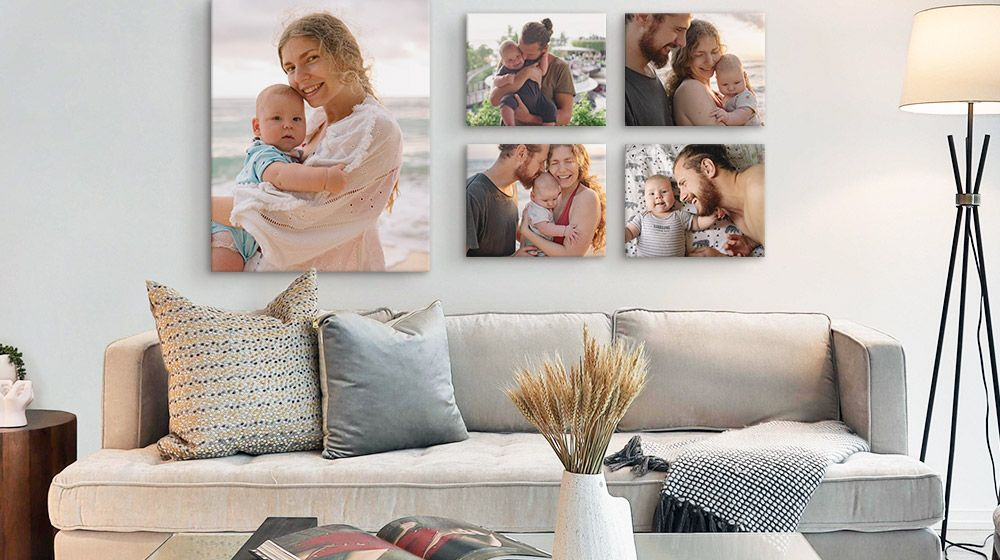 A family wall display of canvas prints featured over a gray couch in a bright living room.