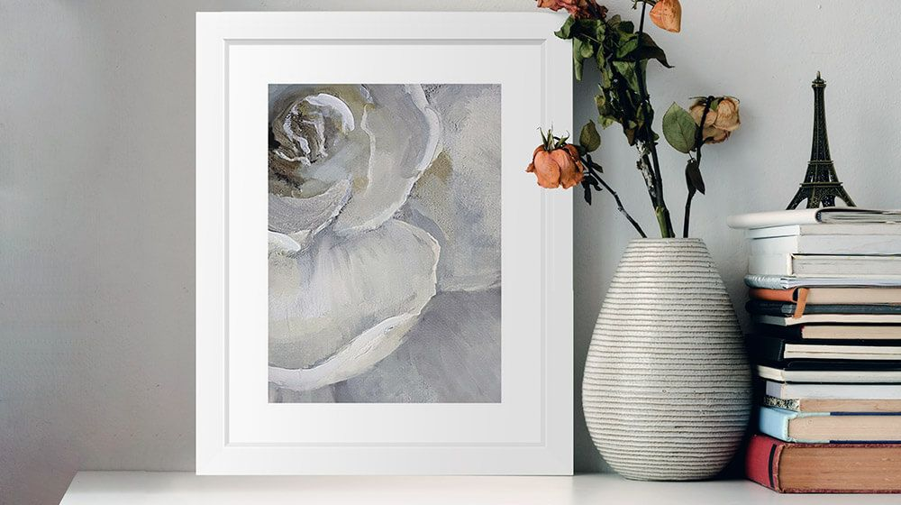 A framed print of a floral art piece sitting on a shelf next to some books