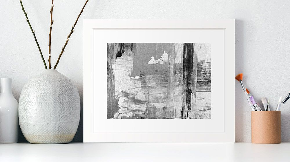 A framed print of an abstract painting sitting on a shelf
